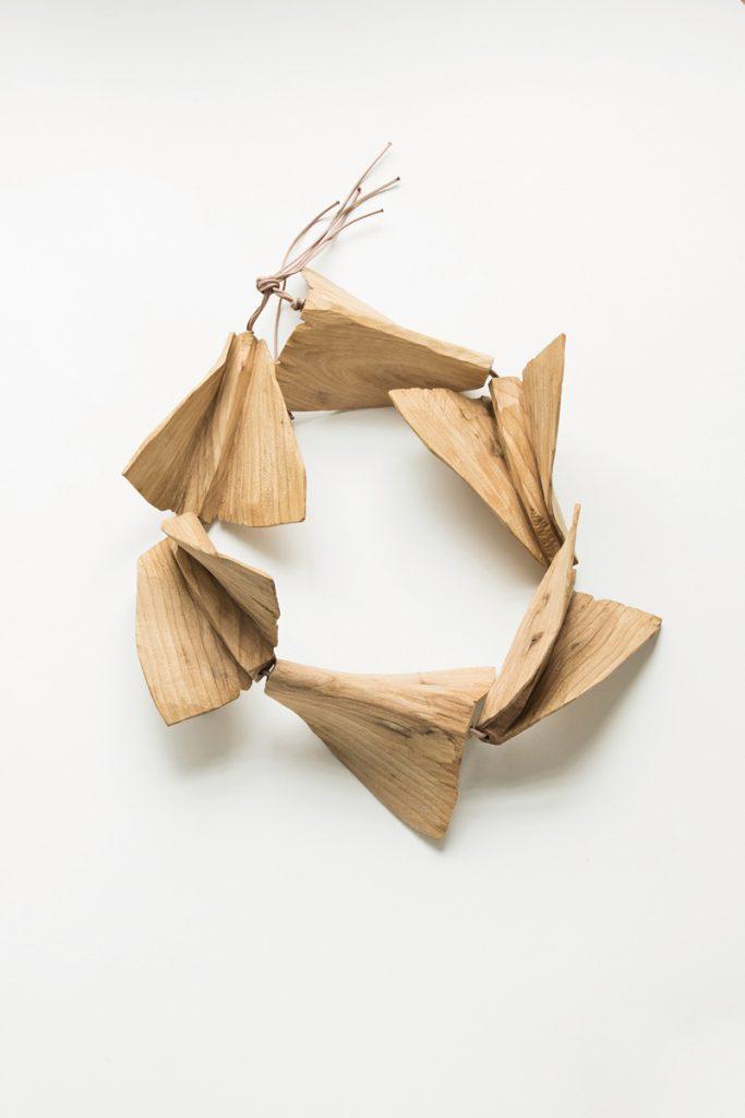 Eine Holzkette aus vielen Holzteilen, die aussehen wie kleine Papierflieger