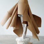 Weiße Gipsfigur mit einem Mantel aus Packpapier auf einem Rollbrett